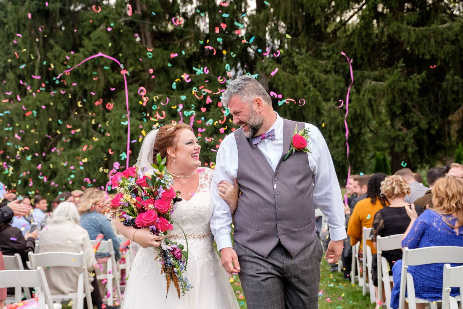Bride and groom walk down the aisle with confetti in the background after farm wedding ceremony.