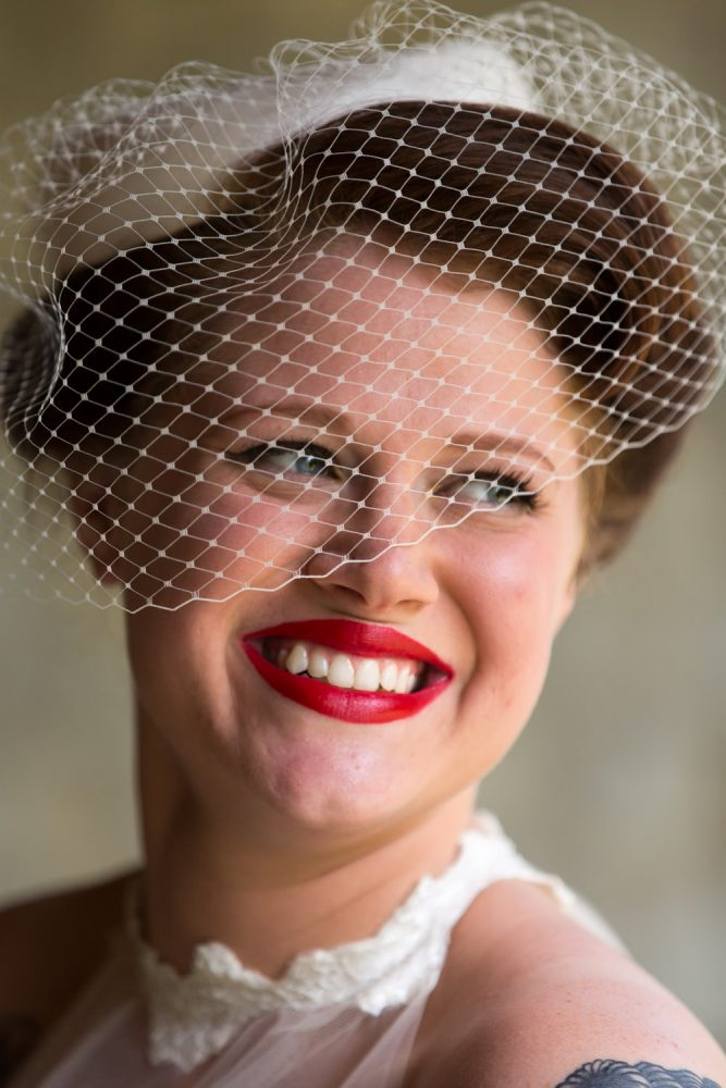Portrait of pin up bride with short lace veil and bright red lipstick.
