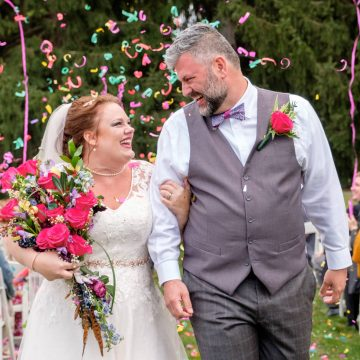 Bride and Groom smiling while walking down the aisle with confetti in the background