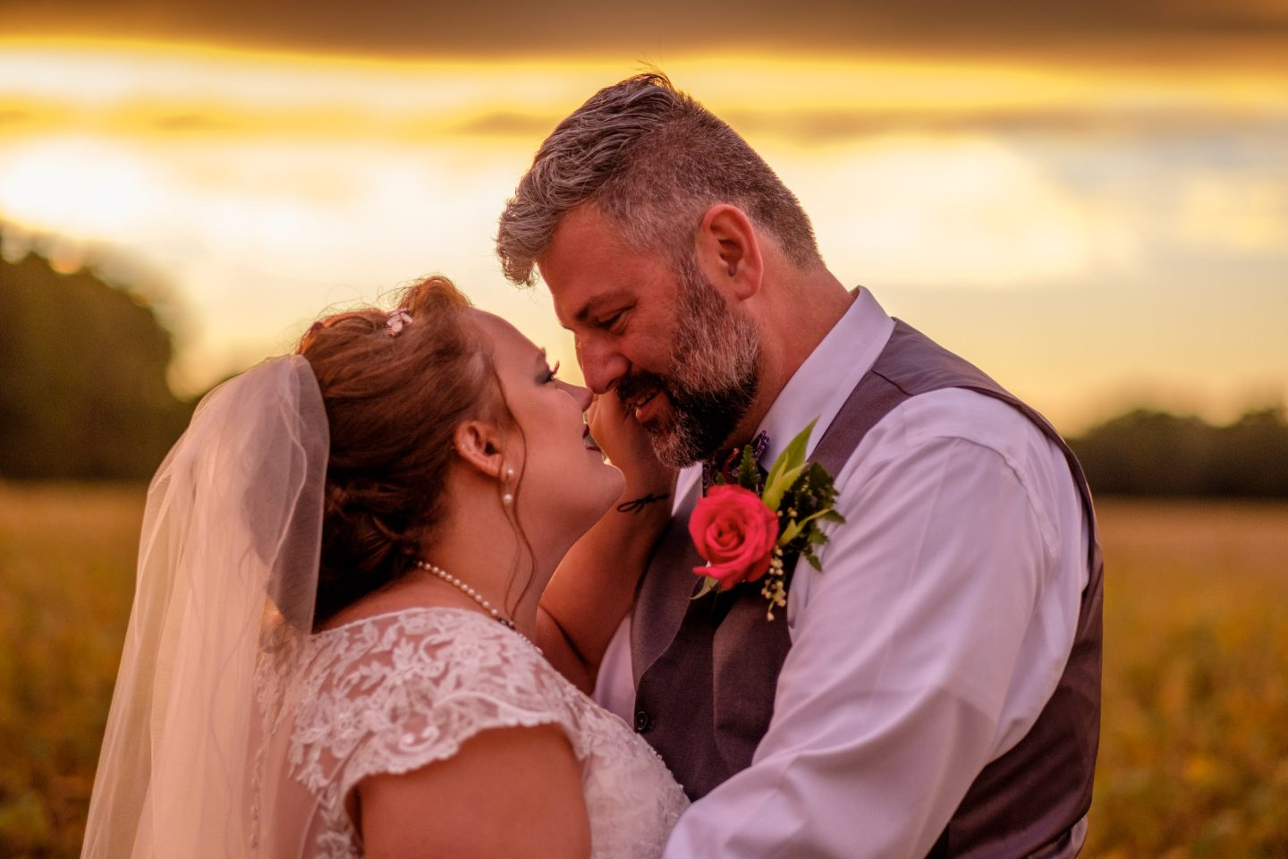 Bride and groom hugging during sunset after farm wedding.