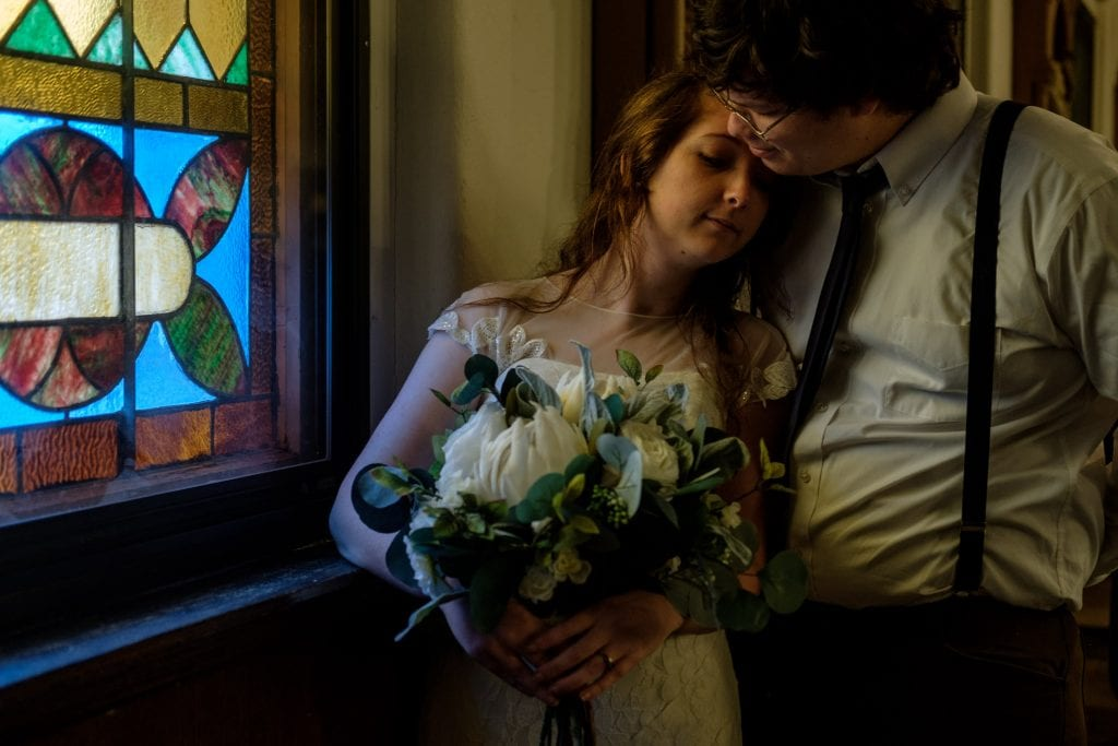 Bride Leans Against Grooms chest with flower bouquet.