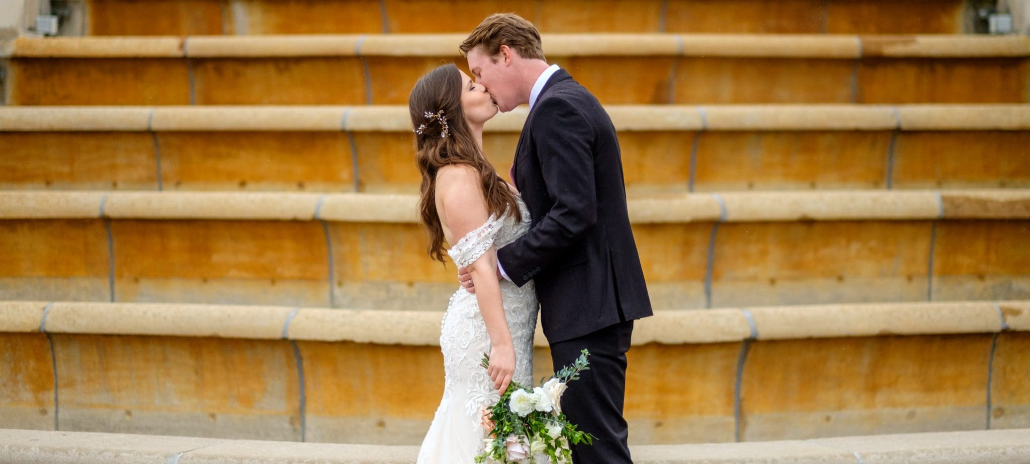 Bride and Groom kiss in front of steps at Ault Park Cincinnati Ohio