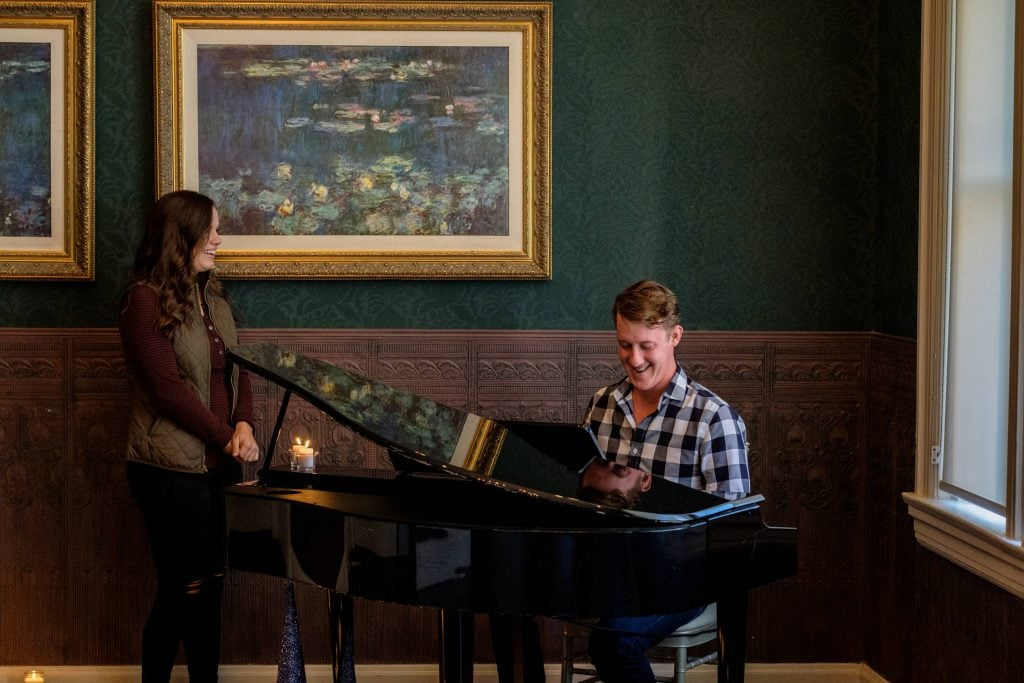 Newly engaged couples laughs as man plays piano.